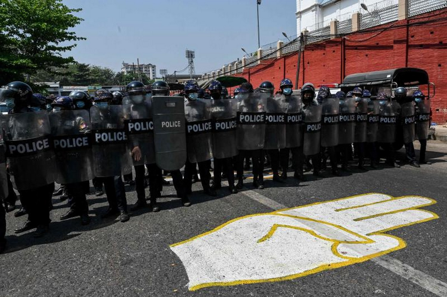 Riot police stand guard on a road, behind a street mural of the protesters' three finger salute, after a clash between pro-junta supporters and anti-military coup protesters in Yangon on Thursday. (Photo: Ye Aung Thu / AFP)