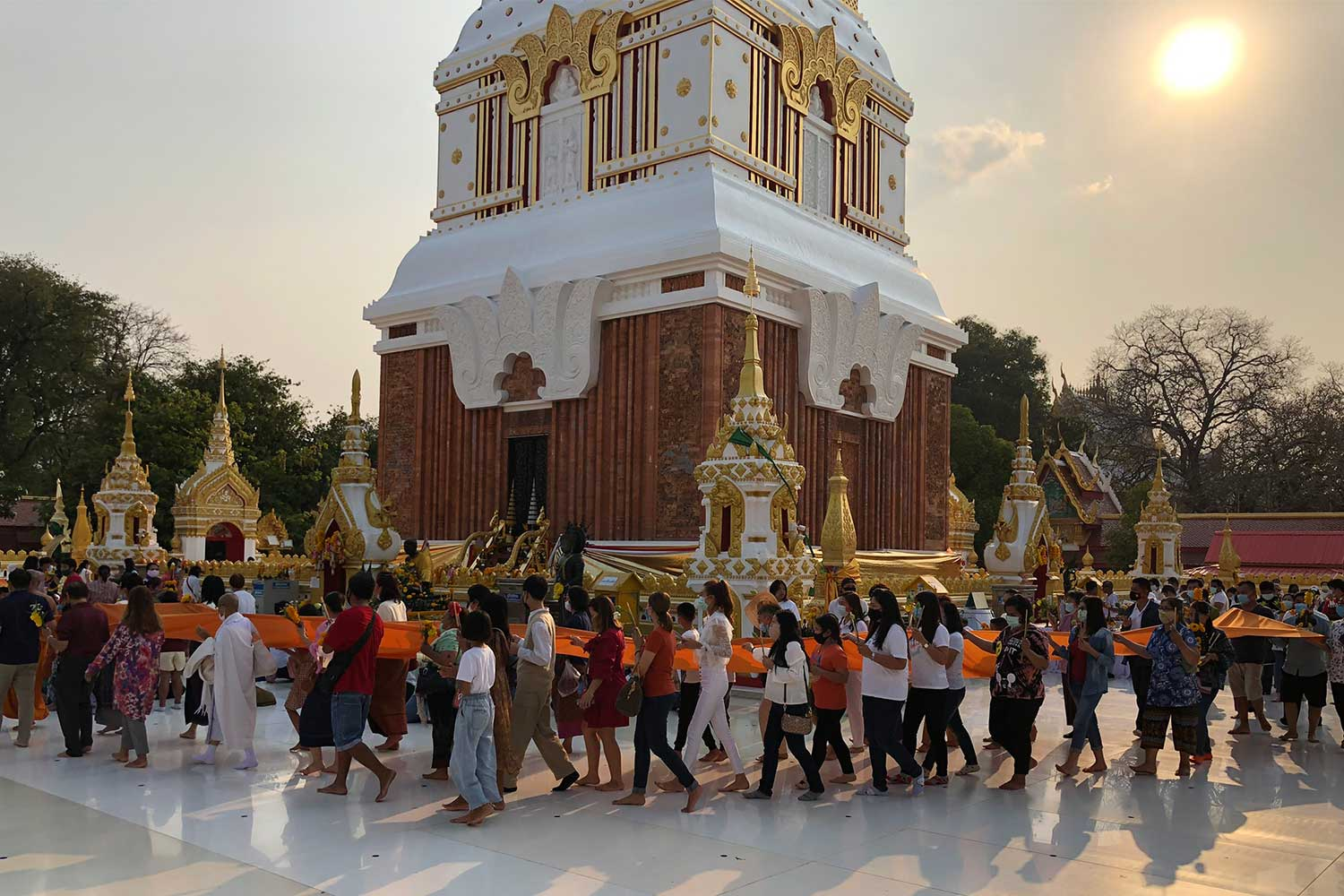 People wearing face masks make merit at Wat Phra That Phanom Woramahawihan near the Mekong River in That Phanom district, Nakhon Phanom province, on Saturday. (Photo by Pattanapong Sripiachai)