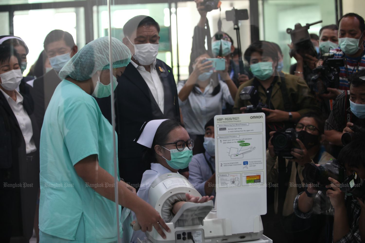 Bangkok Governor Assawin Kwanmuang observes a demonstration of Covid-19 vaccine injection at Bang Khun Thian Geriatric Hospital in Bangkok on Saturday. Vaccinations will begin in high-risk areas nationwide on Sunday. (Photo by Apichart Jinakul)