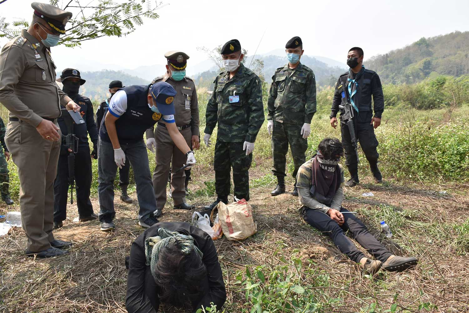 Police and soldiers guard two of the three suspects arrested following  clash with members of a drug caravan in a forest area in Mae Chan, Chiang Rai. (Photo from Pha Muang task force Facebook page)