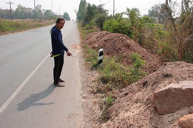 A villager of Ban Moo 12 shows the spot where a backpack containing 30,000 methamphetamine pills was found on a roadside in Nam Phong district of Khon Kaen on Sunday. (Photo by Chakrapan Natanri)