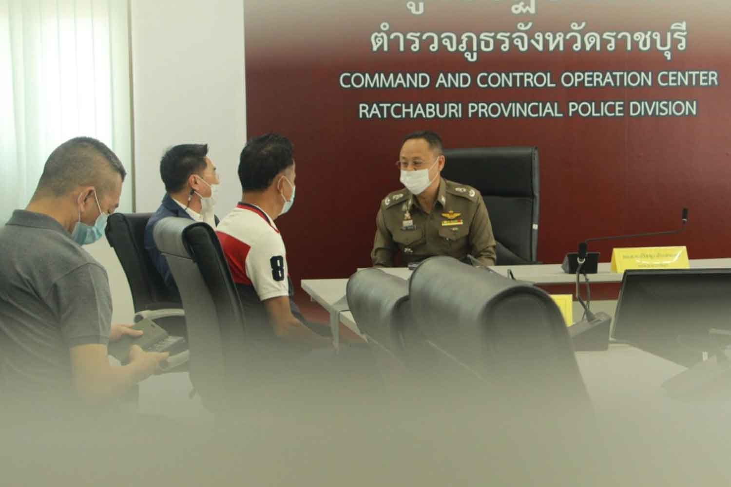 Wanchart Niamraksa, third from left, surrenders to the Ratchaburi police chief on Tuesday. He is the prime suspect in the shooting at a funeral in Photharam district on Monday night which took the life of a mayoral candidate running against his wife, and left six other people wounded. (Photo: Saichol Srinuanchan)