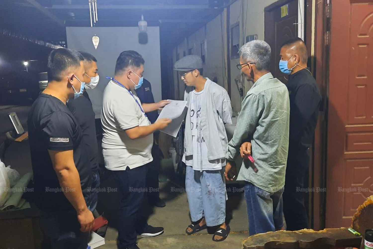 Police arrest singer Chai-amorn Kaewwiboonpan (wearing the hat), aka Ammy The Bottom Blues, at a rented room in Ayutthaya province early on Wednesday morning. (Photo supplied)