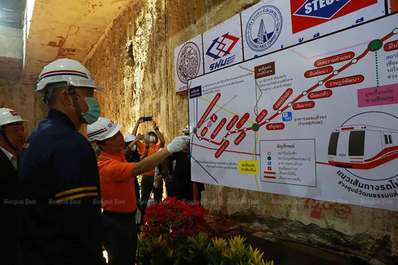 Transport Minister Saksayam Chidchob, left, receives a briefing on the Orange Line construction under Ramkhamhaeng Road in Bangkok in March last year. (Photo by Somchai Poomlard)