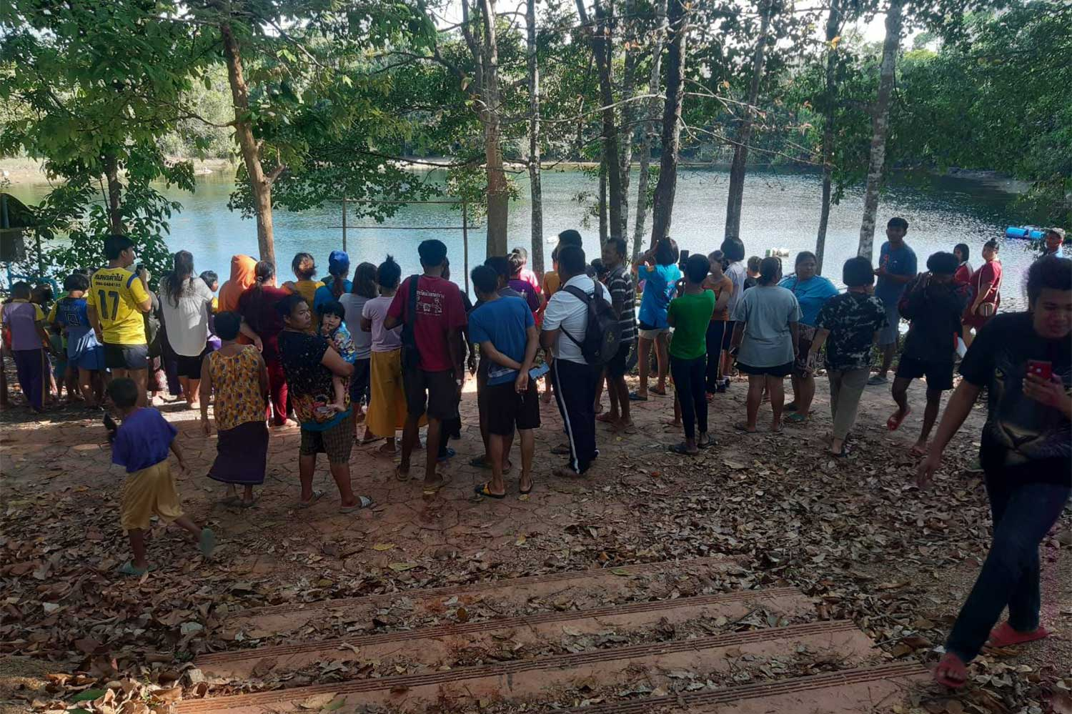Onlookers gather at Talay Songhong Park as rescue workers collect the body of 47-year-old Tosak Warinchaikamon, an experienced diver found dead at the popular cave diving site in Thung Yai district, Nakhon Si Thammarat, on Wednesday afternoon. (Photo: Nujaree Raekrun)