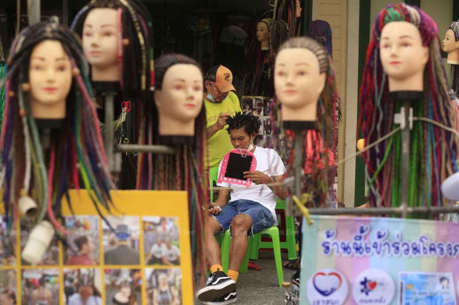 A youth gets his dreadlocks attended to at a hairdresser's on Khao San Road, Bangkok, on Wednesday, when the country recorded one new Covid-19 death and 54 new infections. (Photo: Pornprom Satrabhaya)