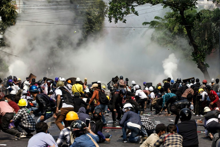 Protesters react as police fire tear gas during a demonstration against the military coup in Mandalay on Wednesday, when 38 people were reported killed by security forces. ( (Photo: STR/AFP)