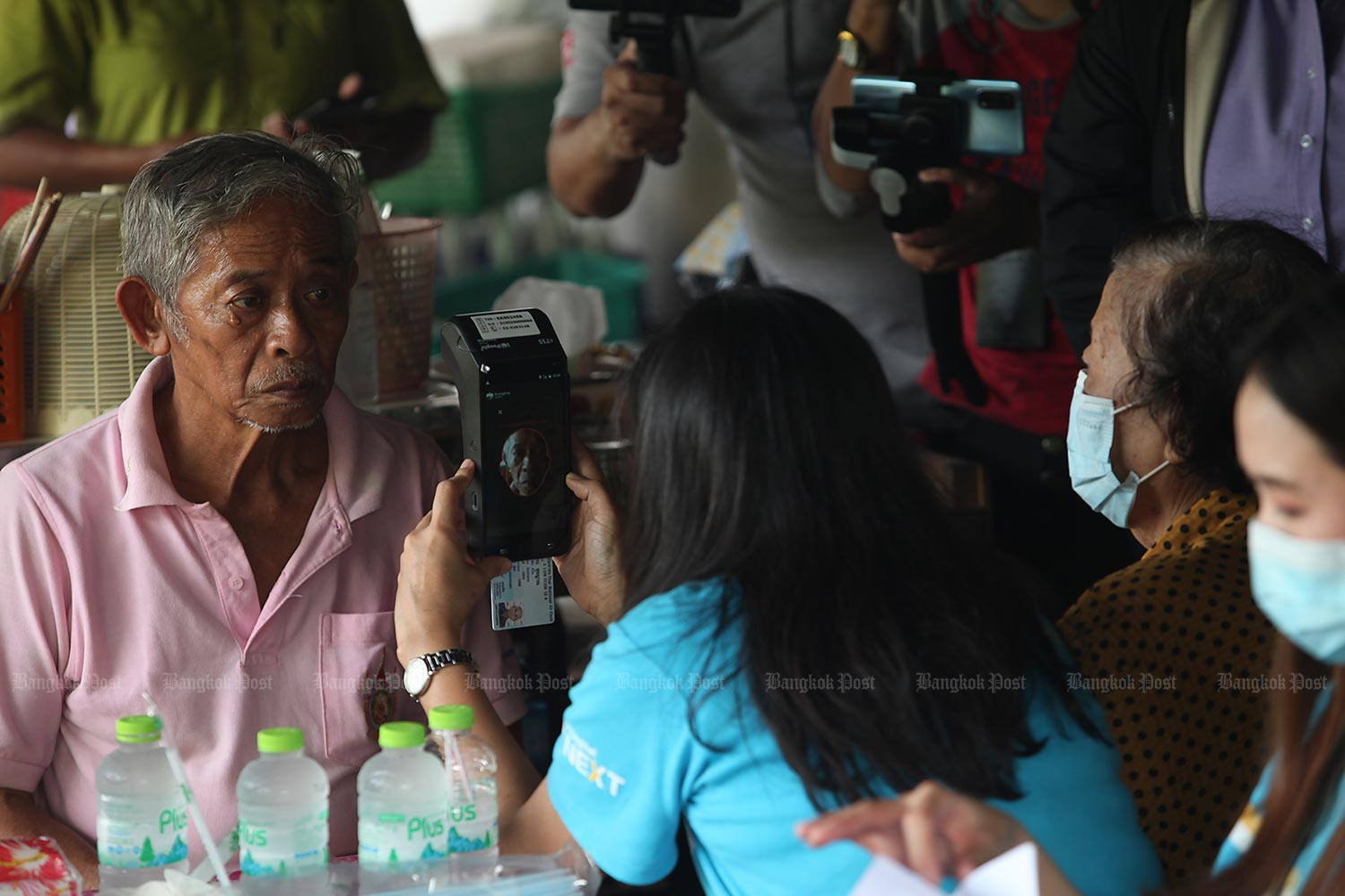A helping hand: A Krungthai Bank staff member helps 70-year-old Jira Sukyan, a resident in tambon Bang Krachao, Samut Prakan's Phra Pradaeng district, register for financial assistance under the Rao Chana (We Win) scheme during a visit organised by the Ministry of Social Development and Human Security. (Photo by Apichart Jinakul)