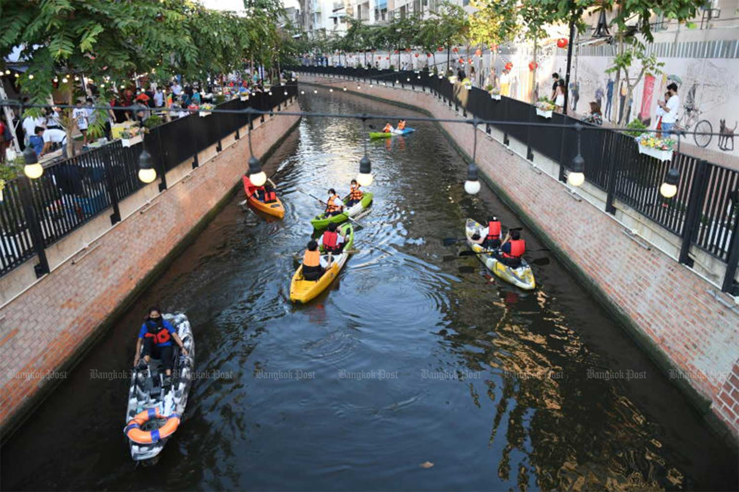 People wearing face masks paddle on Khlong Ong Ang canal in Bangkok. City Hall resumes the service along the canal on Friday after the Covid-19 pandemic situation shows sign of improvement. (Photo: Nutthawat Wicheanbut)