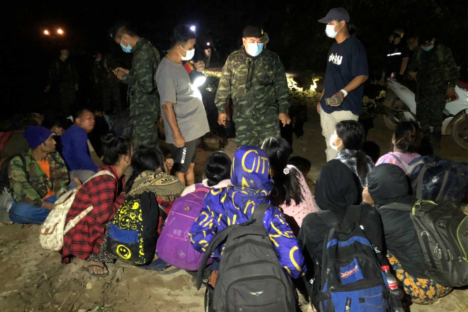 Officers question Myanmar nationals found hiding in a forested area in Sangkhla Buri district of Kanchanaburi late Friday night. (Photo: Piyarat Chongcharoen)