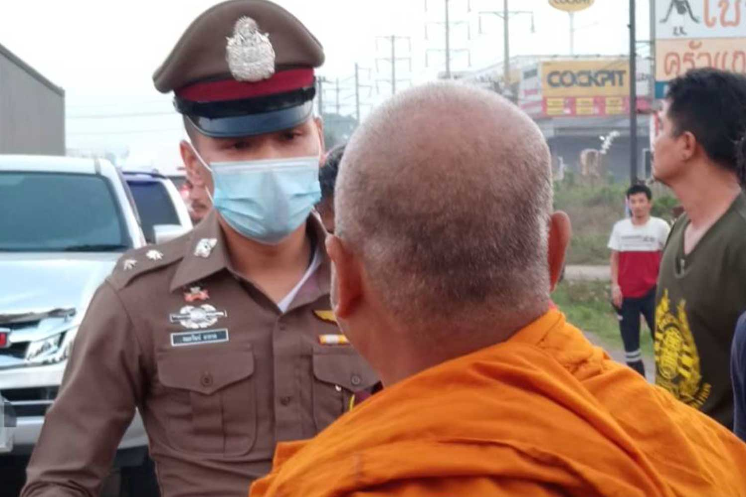 A police officer questions a monk living at the same temple as a 59-year-old monk who was killed after being struck by a pickup while crossing a road in Sri Maha Phot district of Prachin Buri on Saturday morning. (Photo: Manit Sanubboon)