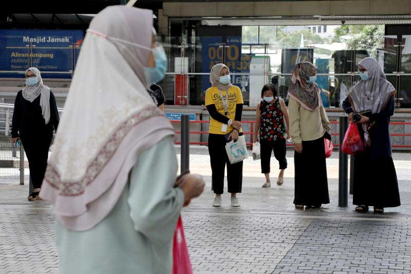People wearing protective masks wait to cross a street in Kuala Lumpur amid the coronavirus disease outbreak in Malaysia on Jan 29, 2021. (Reuters photo)
