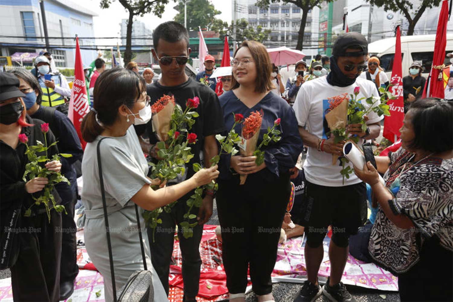 Panupong 'Mike' Jadnok, Panusaya 'Rung' Sithijirawattanakul and Jatupat 'Pai Dao Din' Boonpattararaksa receive flowers from supporters at the Office of the Attorney General  on Monday, before they were transferred to Thon Buri Remand Prison. (Photo: Wichan Charoenkiatpakul)