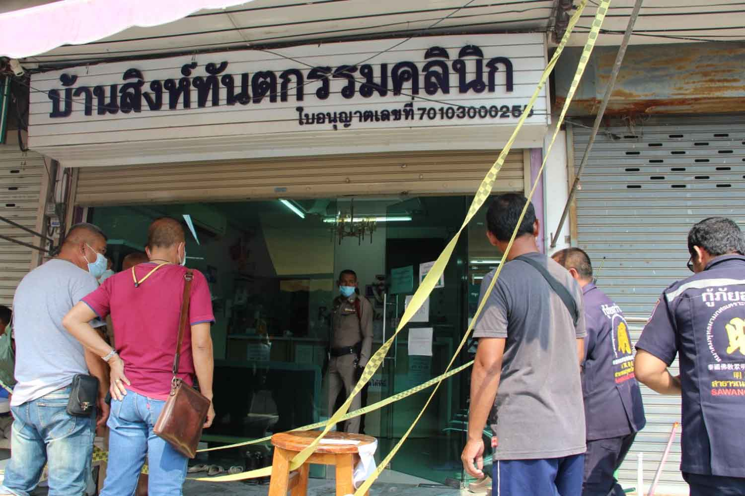 The Ban Sing Tantakam dental clinic in Photharam district, Ratchaburi province, is cordoned off as police examine the murder scene on the second floor, where a man stabbed his estranged lover to death, on Tuesday. (Photo: Saichol Srinuanchan)
