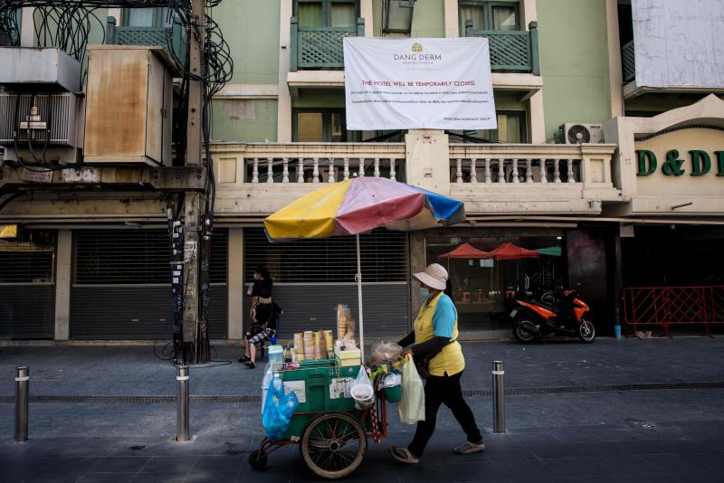 An ice cream vendor pushes a cart past a hotel, temporarily closed due to the Covid-19 coronavirus pandemic, on Khao San Road, a once popular tourist strip in Bangkok on Feb 15, 2021. (AFP file photo)