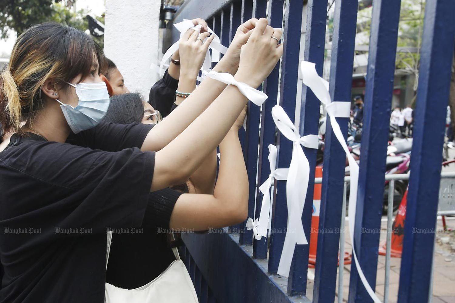 Young protesters dressed in black tie white ribbons on the gates of the Criminal Court on Ratchadaphisek Road on Tuesday after three anti-government protest leaders were indicted and denied bail.(Photo by Apichit Jinakul)