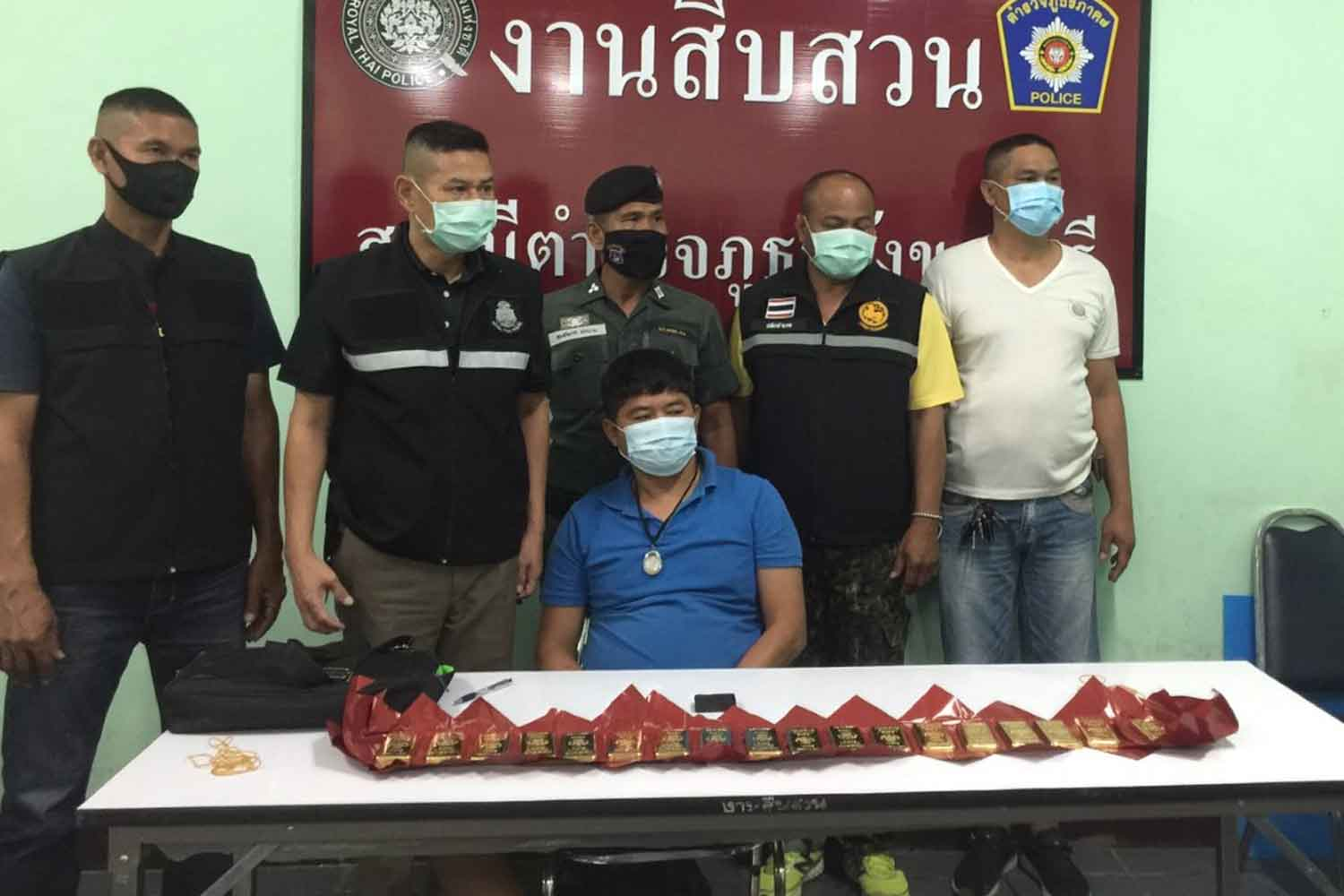Police at Sangkhlaburi station pose for photos with the suspected smuggler and the 18 seized gold bars, on Tuesday. (Photo: Piyarat Chongcharoen)