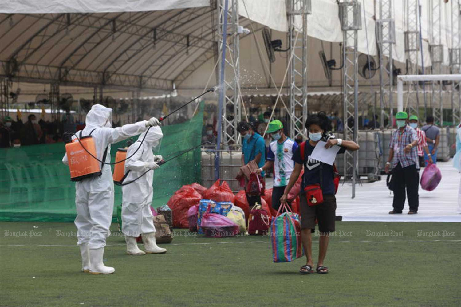 Migrant workers are sprayed with disinfectant as they leave the Covid-19 field hospital at Samut Sakhon's provincial stadium, after completing their quarantine period on Jan 10. (File photo: Arnun Chonmahatrakoo)