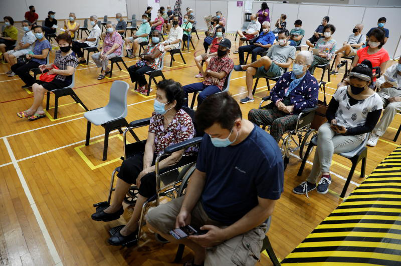People wait at an observation area after their vaccination at a coronavirus disease vaccination centre in Singapore on March 8, 2021.  (Reuters photo)