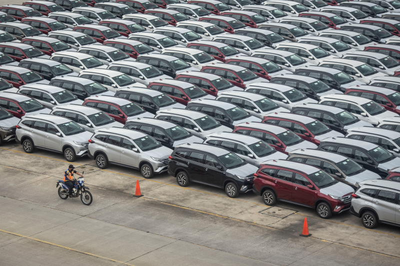 A security officer rides a motorbike as he patrols past new cars parked at the IPC Car Terminal in Jakarta on Feb 11, 2021. (Antara Foto/Reuters photo)