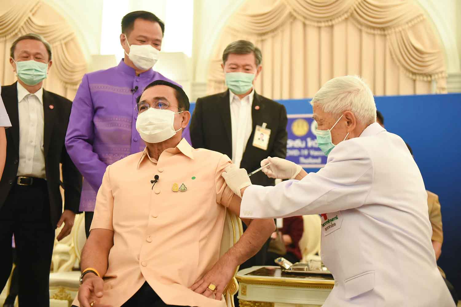 Prime Minister Prayut Chan-o-cha, left, is given the AstraZeneca Covid-19 vaccine by Prof Dr Yong Poovorawan, head of the Centre of Excellence in Clinical Virology, at Government House in Bangkok on Tuesday morning. (Photo from the Covid-19 Information Centre)