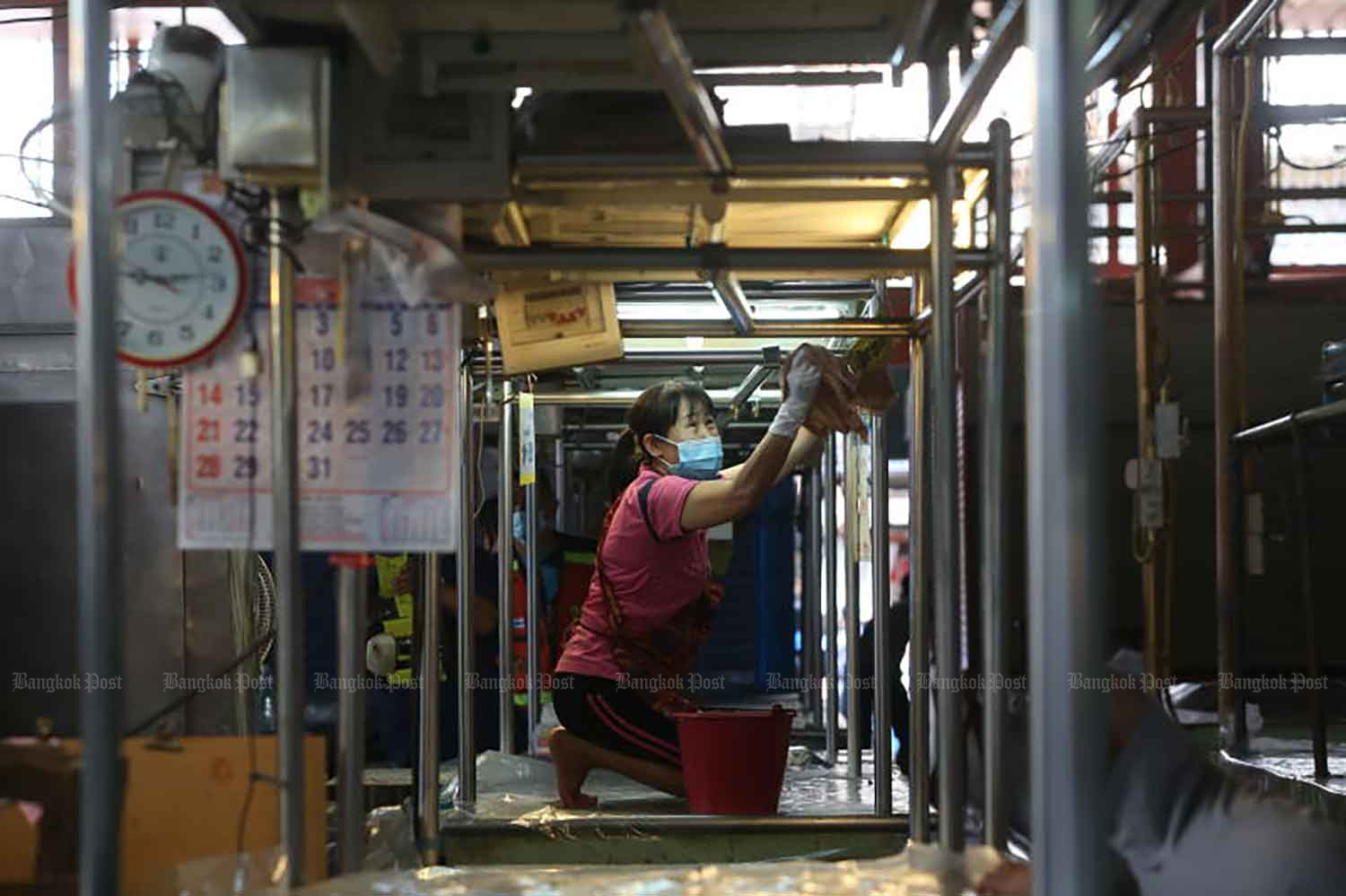 A market vendor in Bangkok's Bang Khae district disinfects her stall on Tuesday after the market was closed as a precaution against Covid-19. City Hall will decide if the market can reopen after three days of mass testing. (Photo: Pattarapong Chatpattarasill)