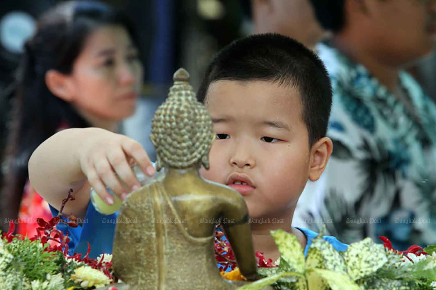 A boy bathes a Buddha figurine during Songkran in Bangkok in 2018. Authorities encourage people to concentrate on similar traditional activities during this year's festival,  because vigorous water splashing will not be allowed. (Bangkok Post file photo)