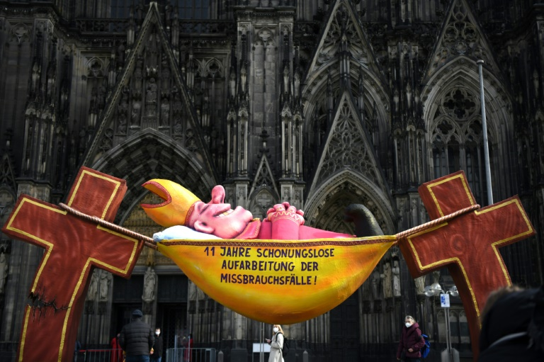 A sculpture by artist Jacques Tilly at Cologne Cathedral bears the slogan '11 years of relentless investigation of the abuse cases!'