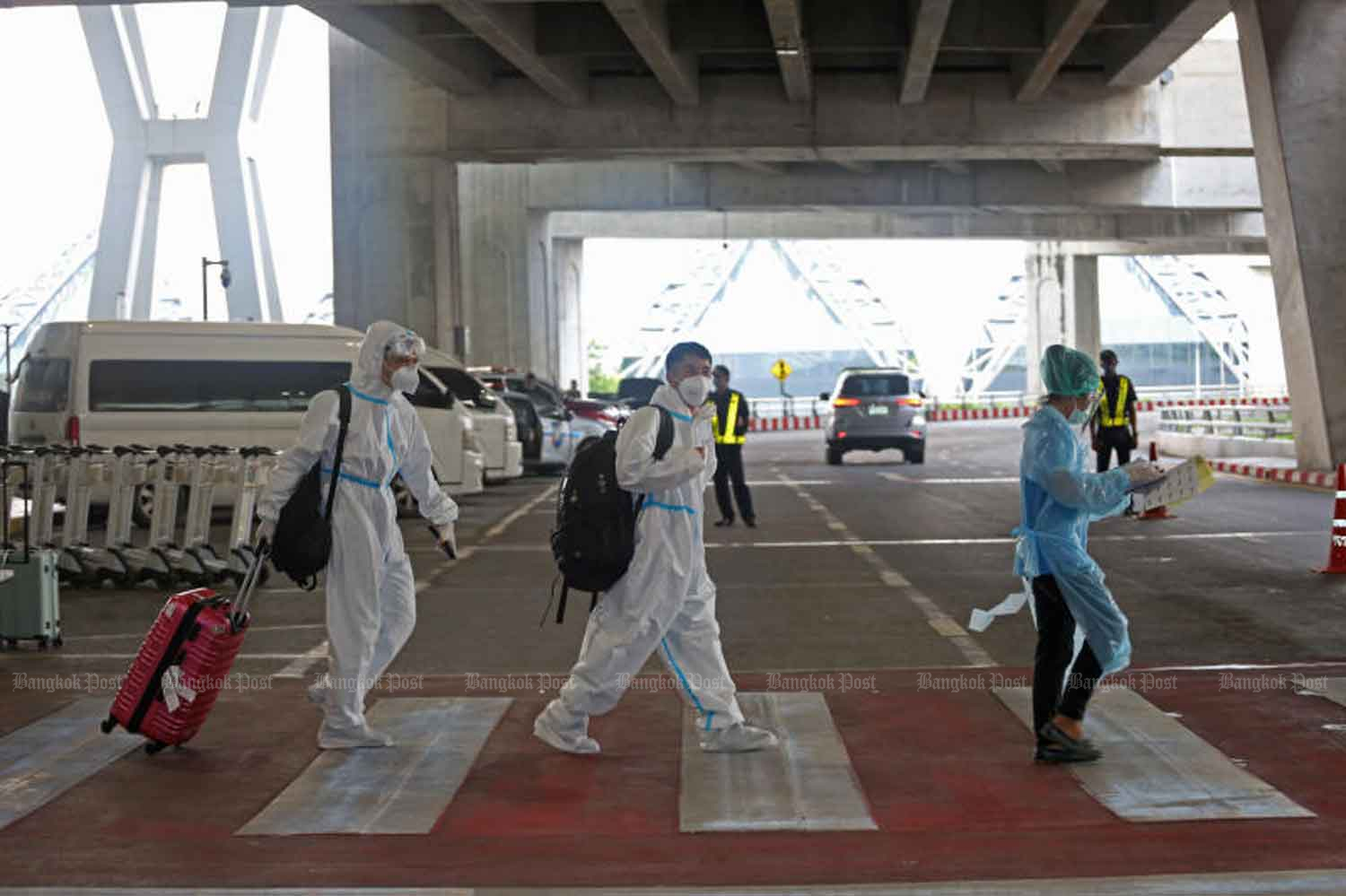 Travellers arrive from overseas in protective gear at Suvarnabhumi airport in Samut Prakan province last October. From next month, quarantine will be shorter and more activities allowed for most arrival from abroad. (File photo)