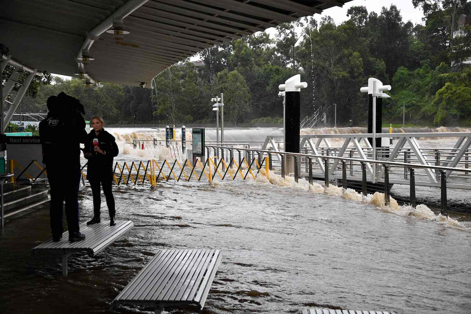 A TV crew films a report beside the overflowing Parramatta River in Sydney on Saturday. (AFP Photo)