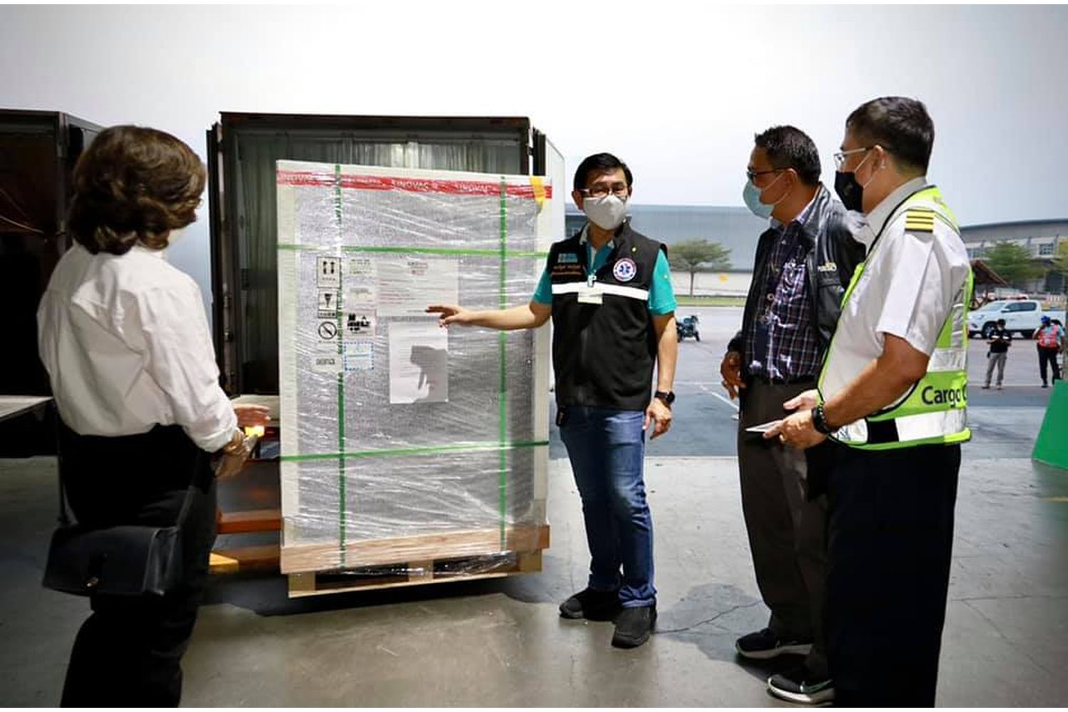 Officials inspect a crate containing some of the 800,000 shots of CoronaVac that arrived at Suvarnabhumi Airport on Saturday. (Photo from อนุทิน ชาญวีรกูล Facebook)
