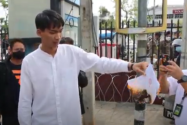 Vachiravich Thetsrimuang burns his summons before entering the Muang district police station in Khon Kaen on Monday on charges arising from protests in Khon Kaen on Feb 12, Feb 20 and March 1. (Photo: Chakkrpan Natanri)