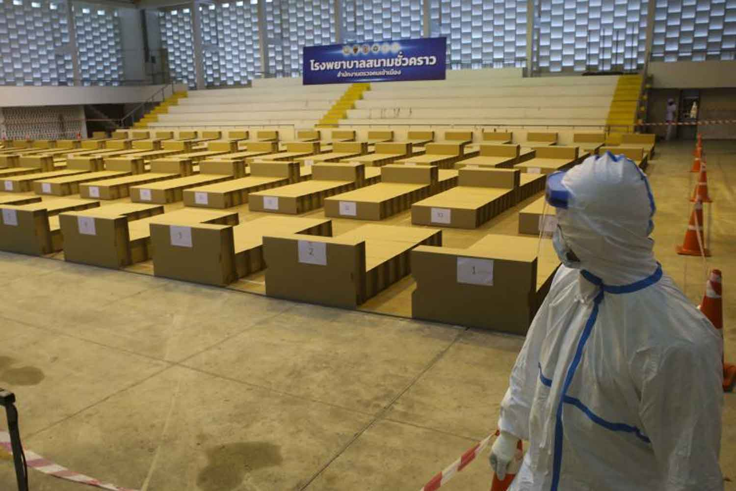 A health worker in protective gear looks at beds in the Boonyachinda Stadium-turned- field hospital on Vibhavadi Rangsit Road, Bangkok, on Monday. The police prepared the temporary facility to handle illegal migrants who contracted Covid-19 in the detention facilities of the Immigration Bureau.  (Photo: Pattarapong Chatpattarasill)