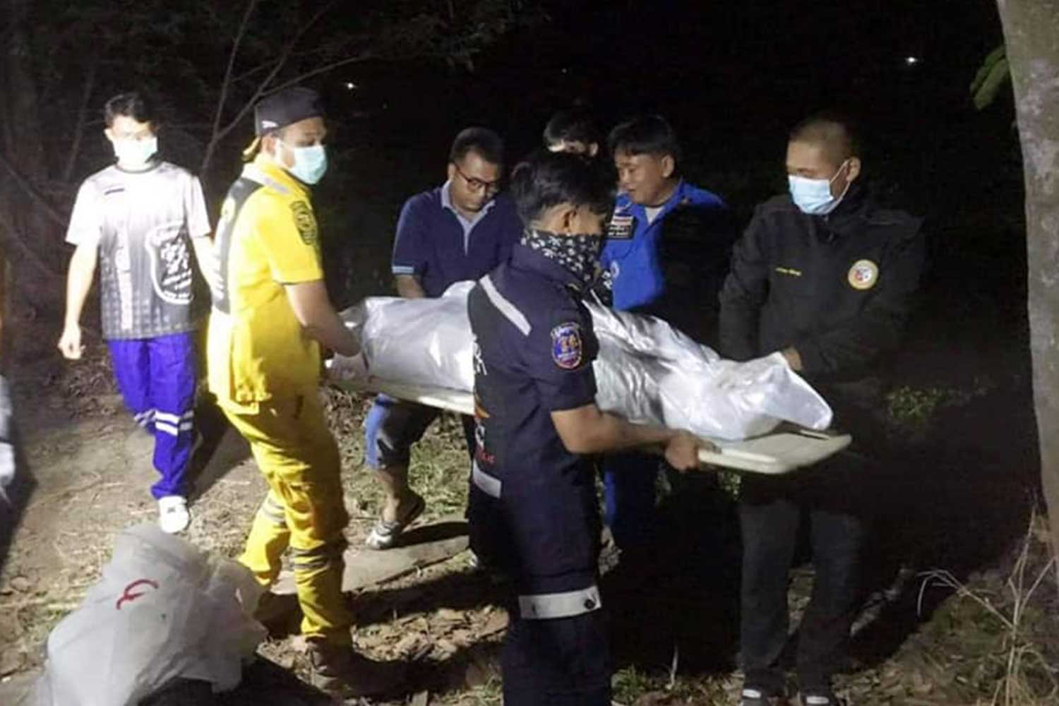 Rescue workers take the wrapped body of the 29-year-old woman from the public pond behind Bueng Hai village in Kamalasai district, Kalasin, on Tuesday night. Her husband was arrested for murder. (Photo: Kudwa Phrathat Yakhu rescue unit Facebook page)