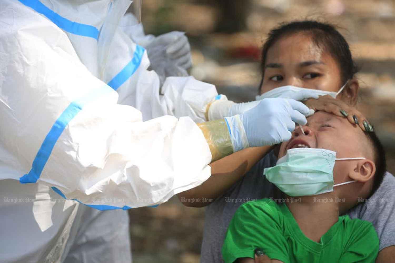 A boy protests as a nasal swab is taken during mass testing for Covid-19 in Bang Khun Thian district of Bangkok on Tuesday. (Photo: Pornprom Satrabhaya)