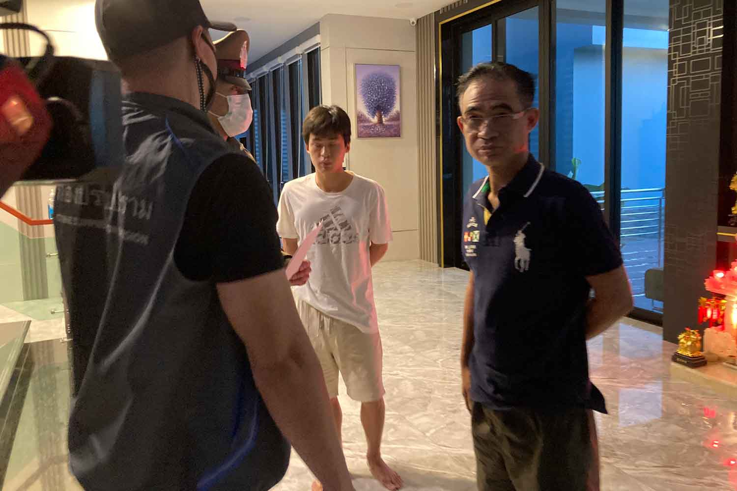 Somchai Jutikitdecha, right, is arrested at his two-rai residence on Rat Bamrung Road in tambon Noen Phra of Muang district, Rayong, about 6am on Friday. His 26-year-old son Thana, centre, was also arrested. (Police photo)