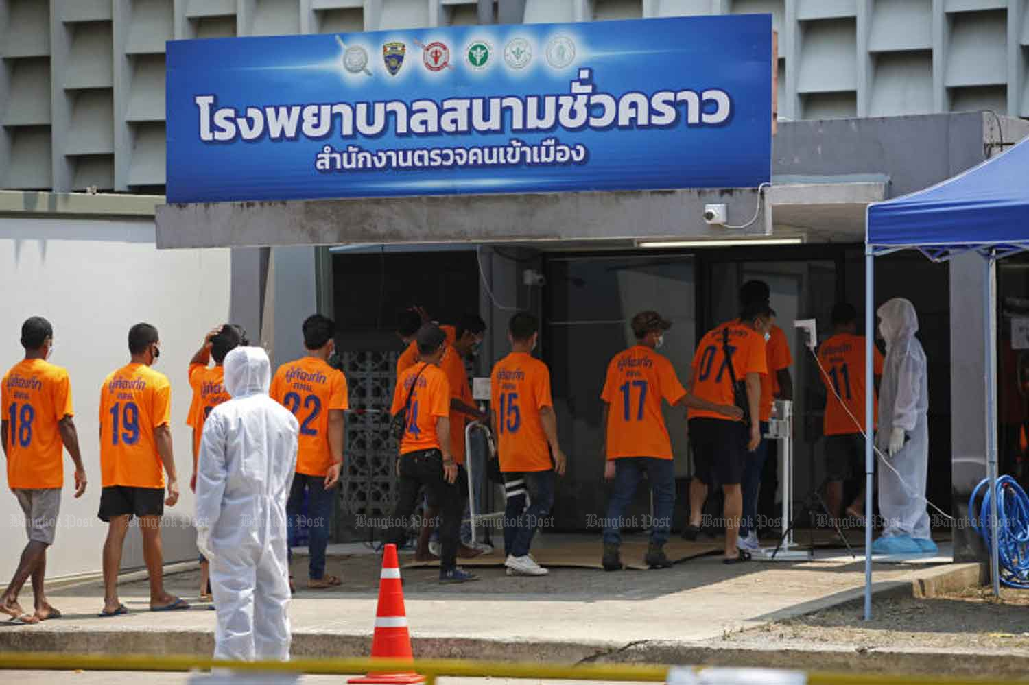 Health workers move 100 Covid-19 infected undocumented migrants from the immigration detention centre in Bang Khen district to the field hospital at the police-owned Boonyachinda Stadium in Laksi district on Wednesday, when the country logged 97 new cases. (Photo: Varuth Hirunyatheb)
