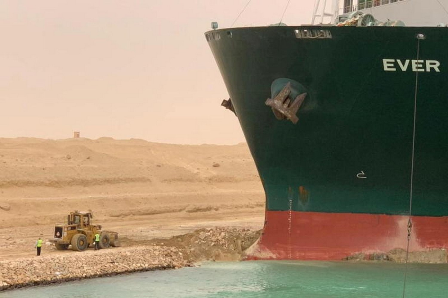 Workers are seen next to the bow of the huge container ship, lodged firmly in the bank of the Suez Canal. (Photo: Suez Canal Authority/Reuters)