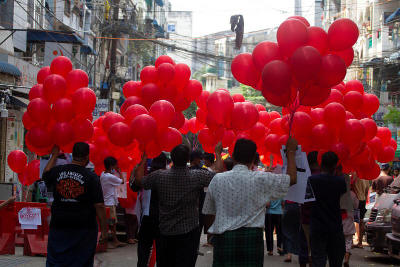 Protesters prepare to release red balloons during a demonstration against the military regime in Yangon on Wednesday. (Reuters photo)