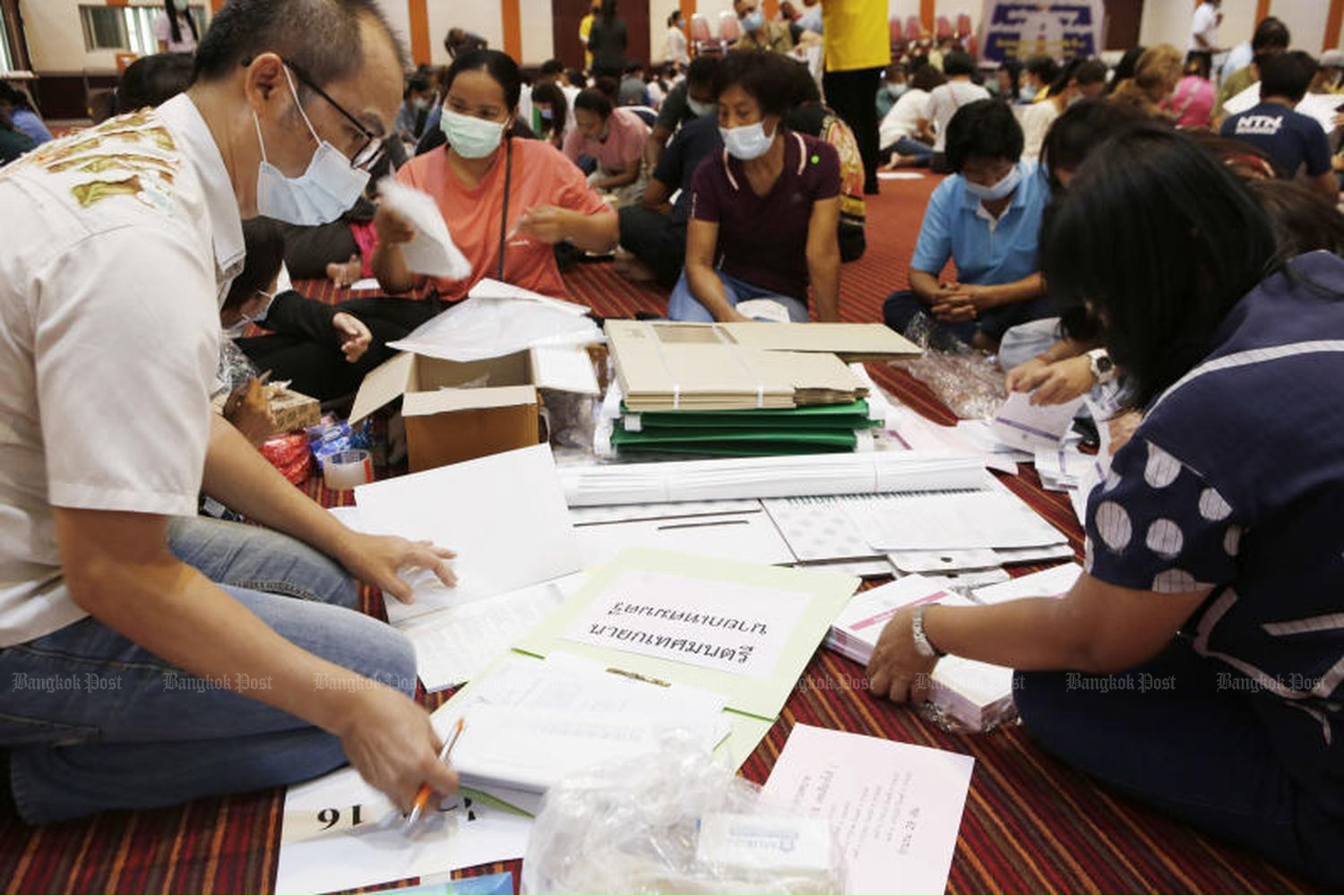 Officials wearing masks check the readiness ahead of the local elections at Rangsit Municipality Office in Thanyabuti, Pathum Thani province, on Saturday. (Photo by Apichit Jinakul)