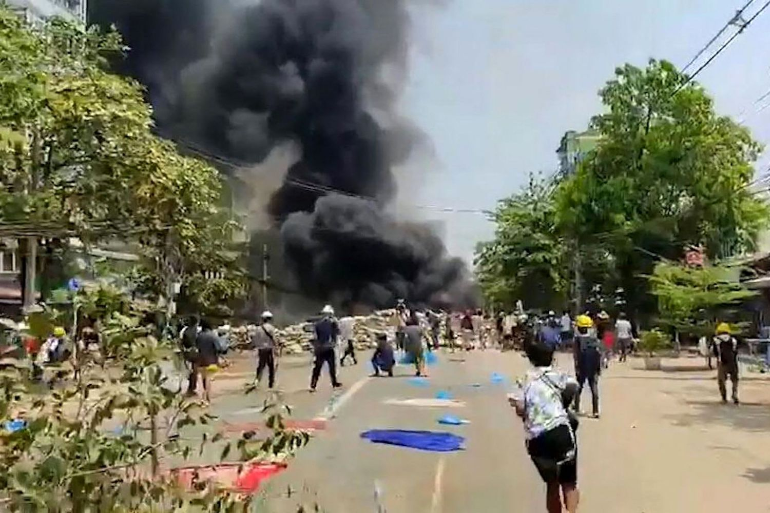 A still from a video taken on Saturday shows protesters watching as smoke rises from a burning barricade during a demonstration against the military coup in Thaketa township in Yangon. (AFP Photo/Anonymous Source Via AFPTV)