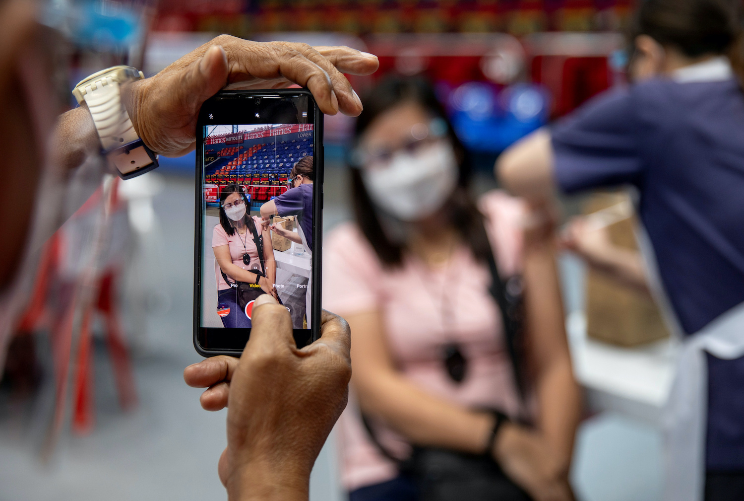 A healthcare worker documents his colleague getting vaccinated in San Juan City, Metro Manila, on March 23. (Reuters Photo)