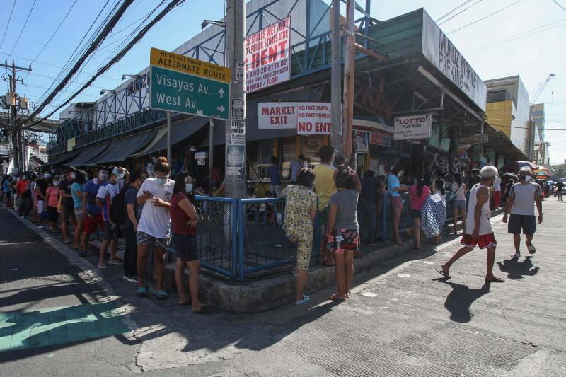 Residents queue up to enter a market in Manila on March 28, 2021, after the Philippines announced that more than 24 million people in and around Manila will go into lockdown next week as hospitals struggle to cope with a surge in Covid-19 coronavirus infections. (AFP photo)