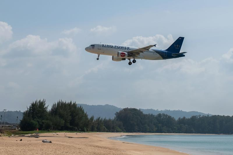 This photo taken on Jan 30, 2021 shows a Thai AirAsia Airbus A320 passenger airplane flying over an empty beach as it lands at Phuket International Airport in Phuket. (AFP photo)