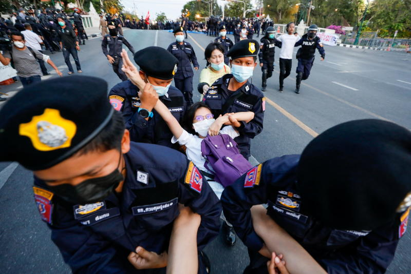 A pro-democracy protester flashes the three-finger salute while she is detained by police officers in front of Government House during a rally demanding the release of arrested protest leaders and the abolition of the 112 lese majeste law, in Bangkok on Sunday. (Reuters photo)