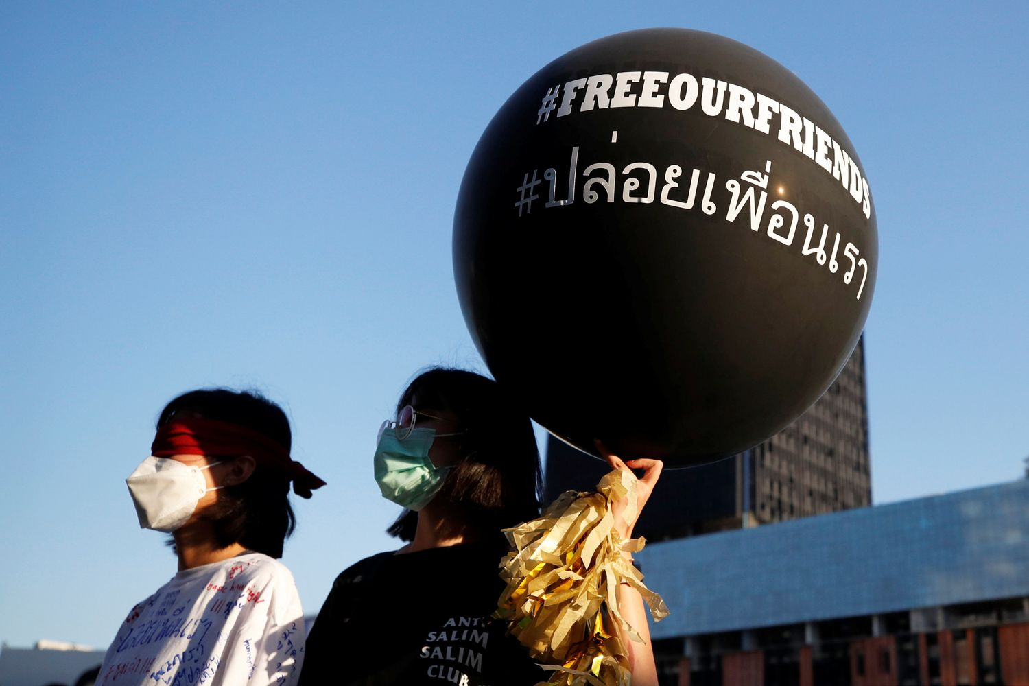 Pro-democracy protesters, one wearing a blindfold, display a hashtagged balloon at a rally demanding the release of arrested protest leaders and the abolition of Section 112 lese majeste law, in Bangkok on Monday. (Reuters photo)