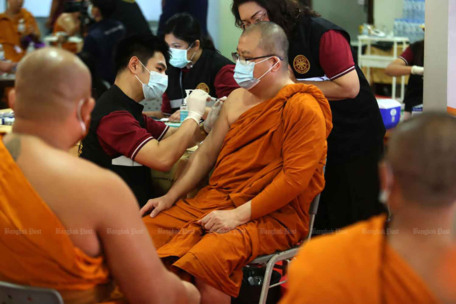 A monk is vaccinated against Covid-19 at Wat Trai Mit Witthayaram on the first day of vaccination for monks in Bangkok on Wednesday. Only those who have passed a health check can receive the vaccine. (Photo: Wichan Charoenkiatpakul)