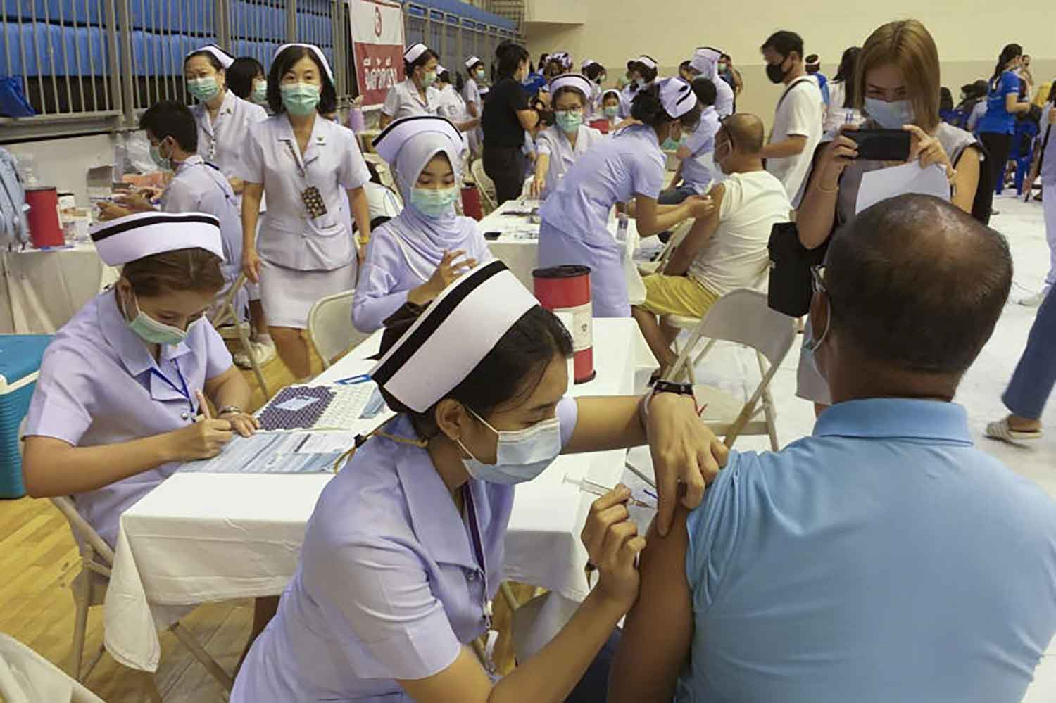 People queue for Covid-19 vaccine inoculations at Saphan Hin gymnasium in Phuket province on Thursday, when 58 new cases were reported nationwide. (Photo: Achadtaya Chuenniran)