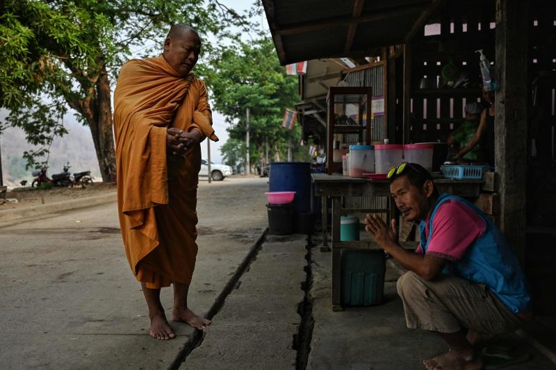 A Karen migrant living Thailand is blessed by a monk in Mae Sam Laep town on the Thai side of the Salween River in Mae Hong Son's Mae Sarieng district on Thursday. (AFP photo)