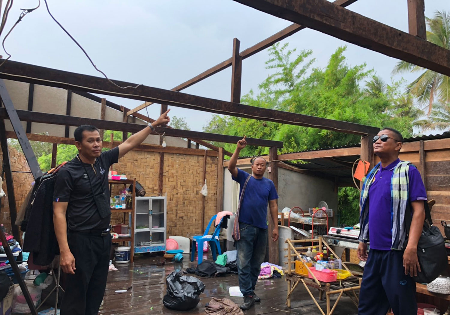 Officials survey a house that lost its roof to high winds during an intense summer storm that struck Nakhon Phanom on Friday evening. (Photo: Pattanapong Sripiachai)